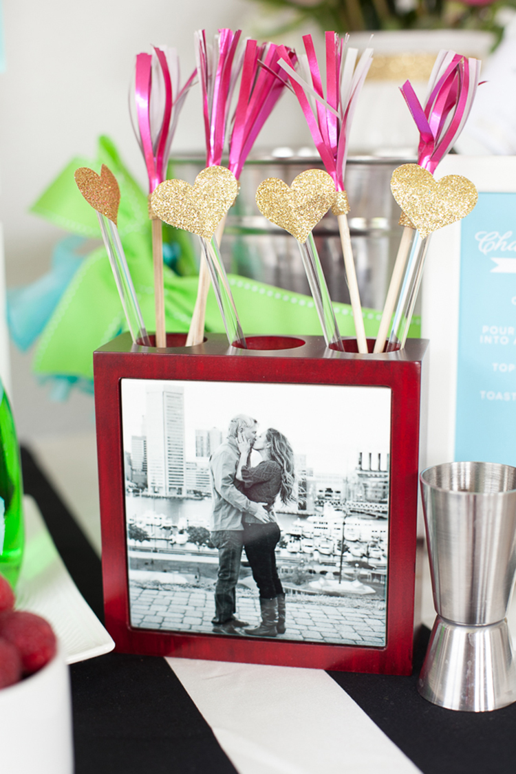 Turn an engagement photo into a unique holder for cocktail stirrers and straws—you can use it to hold pens once the party's over.